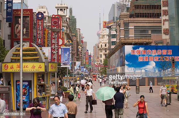 china, shanghai, nanjing road, shoppers walking on pedestrian mall - shanghai billboard stock pictures, royalty-free photos & images