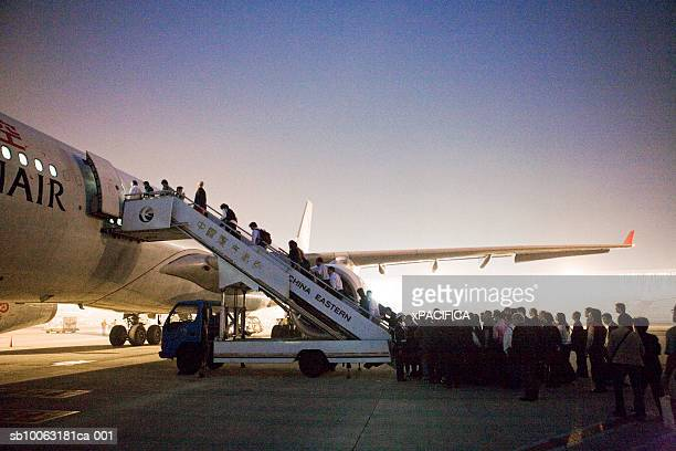China, Shanghai, Pudong Airport, people boarding airplane, dusk