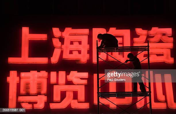 China, Shanghai, two workmen on scaffolding beside neon sign