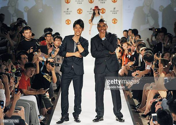 SHANGHAI China Shinji Kagawa of Manchester United poses with teammate Anderson on the runway at a fashion show of a watch brand Hublot in Shanghai on...