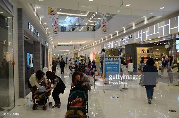 SUZHOU China Shoppers stroll along the aisle in a shopping complex newly opened by Japan's retail giant Aeon Co on the outskirts of Suzhou in China's...