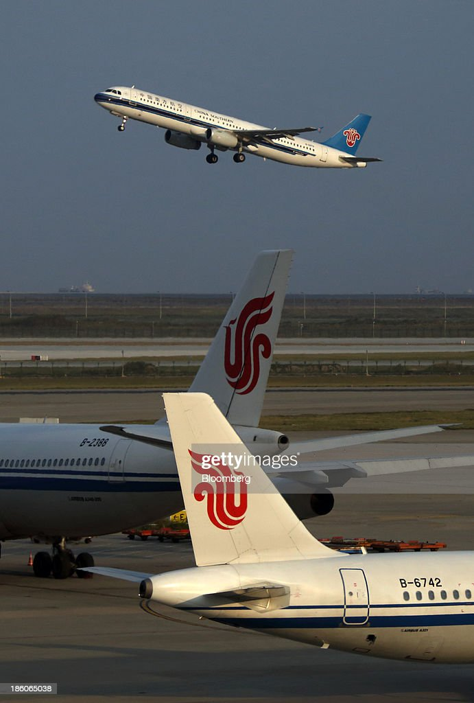 A China Southern Airlines Co. aircraft, top, takes off as Air China Ltd. aircraft stand on the tarmac at Shanghai Pudong International Airport in Shanghai, China, on Saturday, Oct. 26, 2013. Airline profits worldwide in 2013 will be 7.9 percent smaller than estimated at $11.7 billion amid sluggish travel demand and rising oil prices tied to the Syria crisis, the International Air Transport Association said last month. Photographer: Tomohiro Ohsumi/Bloomberg via Getty Images