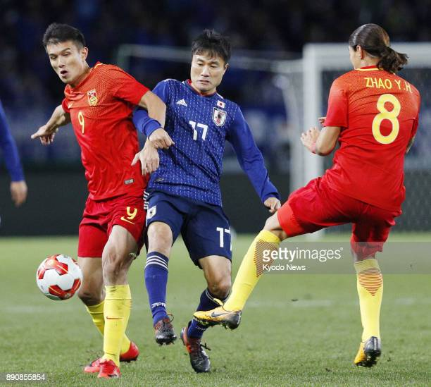 China striker Xiao Zhi vies for the ball with Japan midfielder Yasuyuki Konno during the first half of a men's match in the E1 Football Championship...