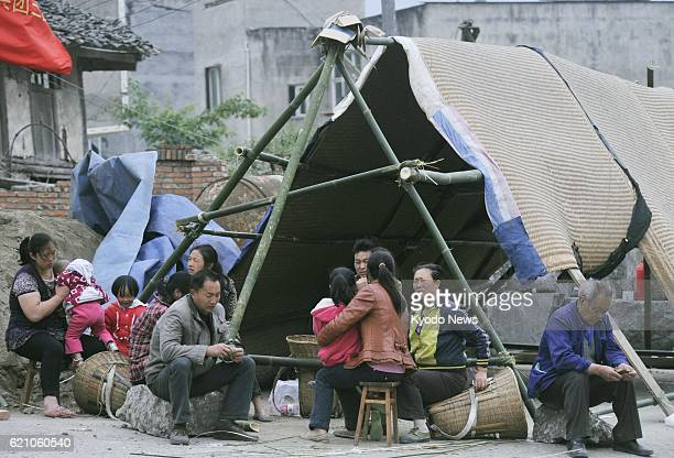 YA'AN China Survivors rest at a handmade tent near their damaged home in the Lushan county area of Ya'an in the southwestern Chinese province of...