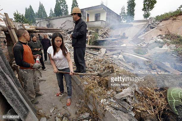 YA'AN China Survivors try to clean rubble near their damaged home in the Lushan county area of Ya'an in the southwestern Chinese province of Sichuan...