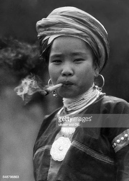 China The New Year celebrations Portrait of a girl of the tribe Lahu smokig a thick cigarette made of leaves ca 1942 Photographer Hugo Adolf...