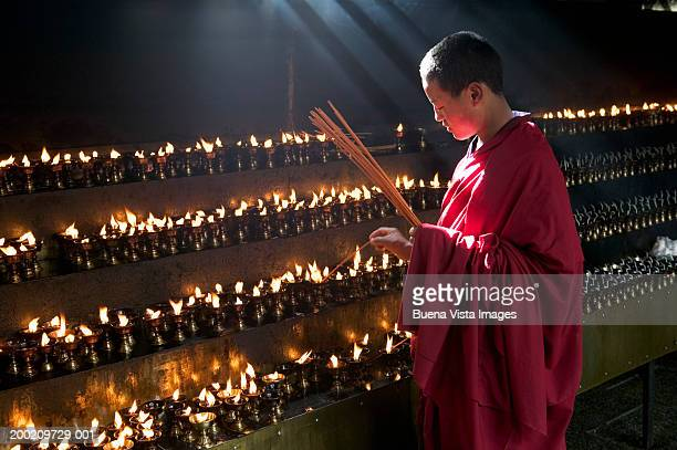 China, Tibet, Buddhist monk lighting insense at Jokhang monastery