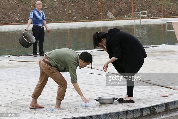 YA'AN China Women wash their faces with water from an outdoor pool in Lushan county in Ya'an in the southwestern Chinese province of Sichuan on April...