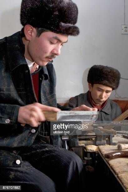 China Xinjiang Kashgar Zwei junge Uiguren bei der Ausbildung zum Bau von Musikinstrumenten | Two young uigury men learning how to build...