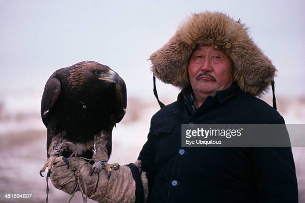 China Xinjiang Province People Kazakh man wearing thick fur lined hat and holding eagle on his gloved hand