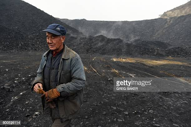 ChinaeconomyenvironmentcoalclimateFOCUS by Tom HANCOCK In this photo taken on November 20 a worker walks past piles of coal near a coal mine at...