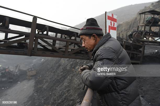 ChinaeconomyenvironmentcoalclimateFOCUS by Tom HANCOCK In this photo taken on November 20 a worker watches over activities near a coal mine at Datong...