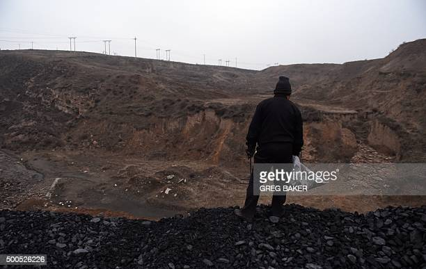 ChinaeconomyenvironmentcoalclimateFOCUS by Tom HANCOCK In this photo taken on November 20 a woman stands on a pile of coal near a coal mine at Datong...