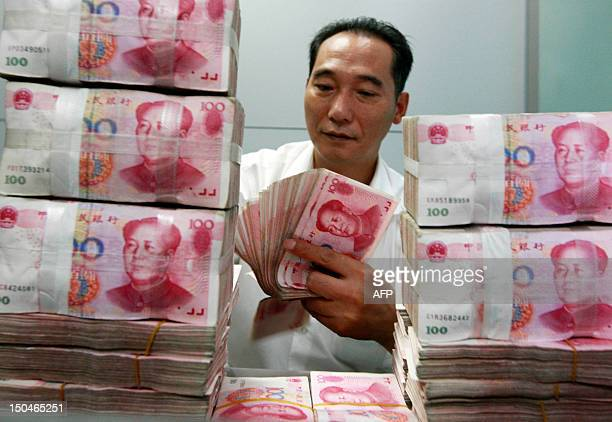 ChinaeconomyforexFOCUS This picture taken on August 17 2012 shows a Chinese bank staff member counting stacks of 100yuan notes at a bank in Huaibei...