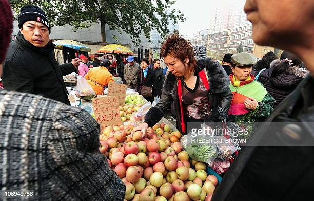 ChinaeconomyinflationconsumersFOCUS by Allison Jackson People shop for produce from a vendor at an outdoor vegetable and fruit market in Beijing on...
