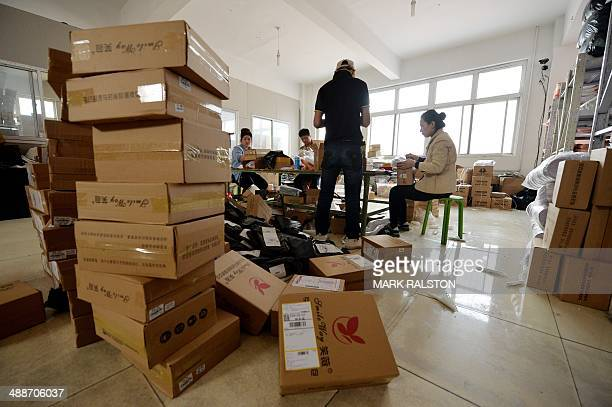 ChinaeconomyretailAlibabafamilyFOCUS by Tom HANCOCK This image taken on April 24 2014 shows workers at a handbag factory packaging up orders to be...