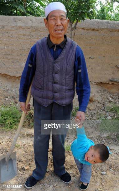 China-economy-society-migration,FEATURE by Sebastien Blanc In a picture taken on September 20, 2011 an elderly man poses with his grandson outside...