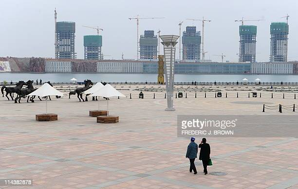 STORY 'ChinaeconomysocietypropertyFEATURE' by Allison JacksonPedestrians walk along a deserted plaza in Kangbashi a district on the outskirts of...