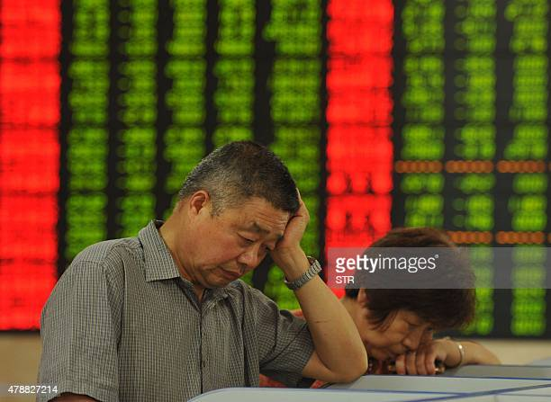 Chinaeconomystocks FOCUS by Fran Wang This photo taken on June 26 2015 shows investors checking the share prices in a stock firm in Fuyang east...