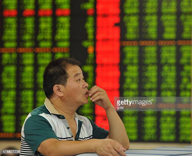 Chinaeconomystocks FOCUS by Fran Wang This photo taken on June 26 2015 shows an investor checking the share prices in a stock firm in Fuyang east...