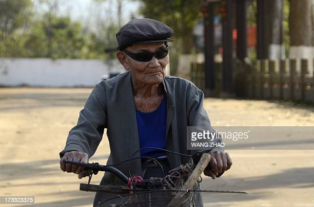 ChinahealthpeopleageingsocialFEATURE This picture taken on January 22 2013 shows an elderly man riding a bicycle along a road in Chengmai city in...