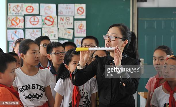 ChinahealthsmokingtobaccoADVANCER by Etienne LAMY A teacher talks to children in her class during an antismoking lecture in an elementary school in...