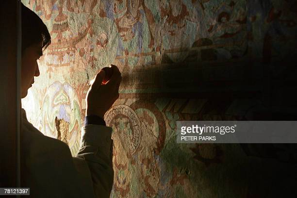 China-heritage-archaeology-religion-Mogaoby Dan Martin In the cool gloom of a sandstone cavern a restorer painstakingly applies a liquid bonding...