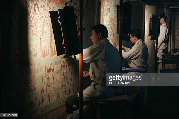 China-heritage-archaeology-religion-Mogaoby Dan Martin In the cool gloom of a sandstone cavern restorers work on crumbling 000-year-old Buddhist...