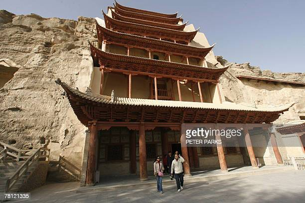 China-heritage-archaeology-religion-Mogaoby Dan Martin Visitors walk outside the Mogao Grottoes Buddhist mural complex in remote Gansu province in...