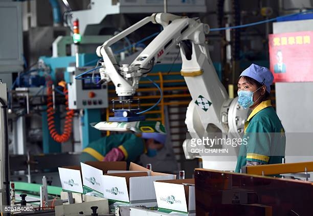 ChinaIslamfoodpoliticssocialFEATURE by Benjamin HAAS This picture taken on September 23 2015 shows workers at an assembly line sealing bags of rice...