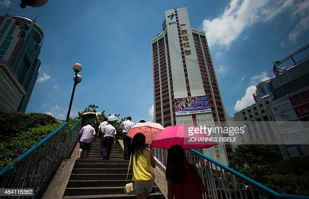 ChinalanguagepoliticsGuangdongFEATURE by Felicia SONMEZ This photo taken on August 11 2014 shows a pedestrian walking past the headquarters of GDTV...