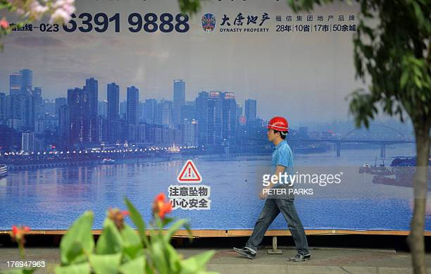 WITH 'ChinapoliticscorruptionBoADVANCER' BY This photo taken on August 8 2013 shows a construction worker passing a poster of the sweeping views of...