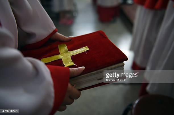 ChinareligionpoliticsCatholicFEATURE by Tom HANCOCK This photo taken on May 24 2015 shows an altar server holding a text during a celebration of the...
