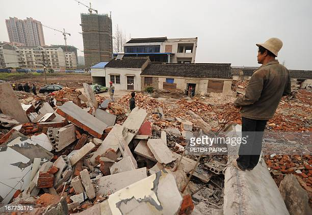 ChinarightspoliticscorruptionFEATURE by Neil Connor This picture taken on March 13 2013 shows a worker looking out over the rubble where 75yearold...