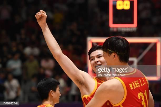 China's Abudurexiti Abudushalamu and China's Wang Zhelin celebrate during the men's gold medal basketball match between Iran and China at the 2018...