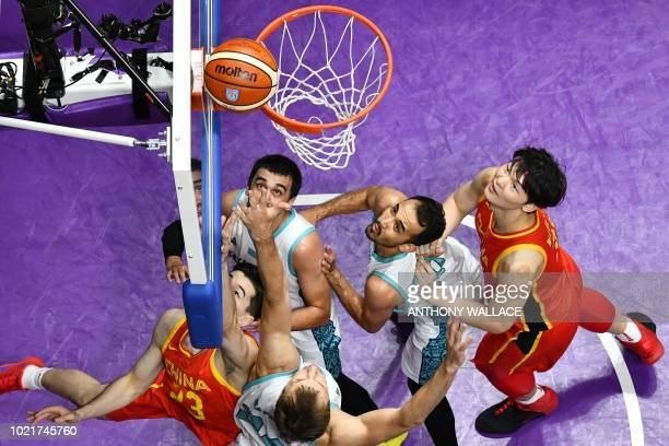 China's Abudushalamu Abudurexiti shoots during the men's preliminary round Group D basketball match between Kazakhstan and China at the 2018 Asian...