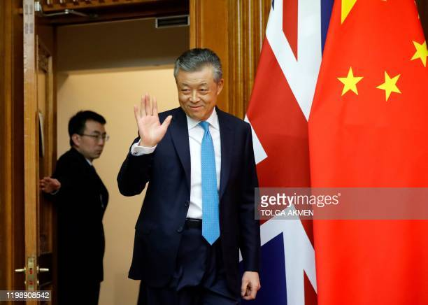 China's ambassador to Britain Liu Xiaoming passes a Union flag and the national flag of China as he arrives to speak to members of the media at the...