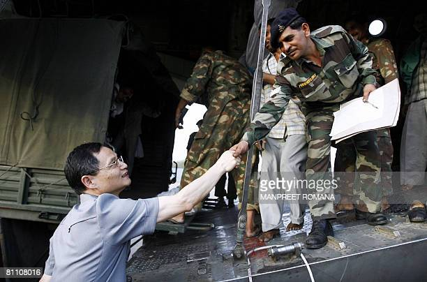 China's ambassador to India Zhang Yan shakes hands with an Indian army officer loading relief material for earthquake affected people in China on...