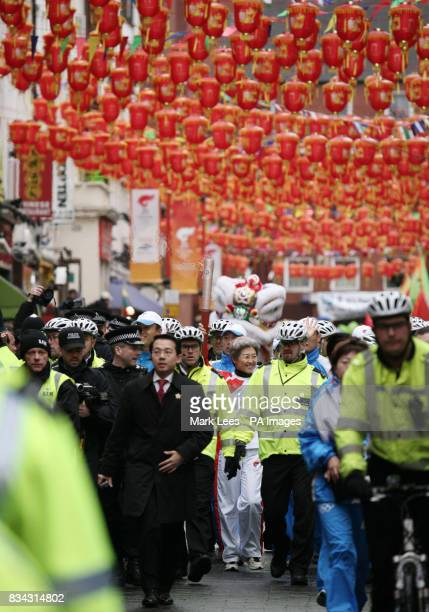 China's Ambassador to the United Kingdom Fu Ying carries the Olympic torch through London's Chinatown during part of its journey across London on its...