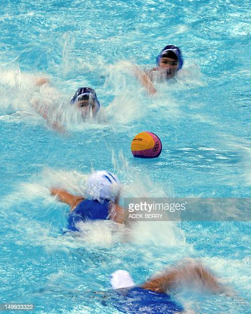 China's and Italy's water polo players race to the ball during their women's water polo classification 5th/8th round match against Italy at the...