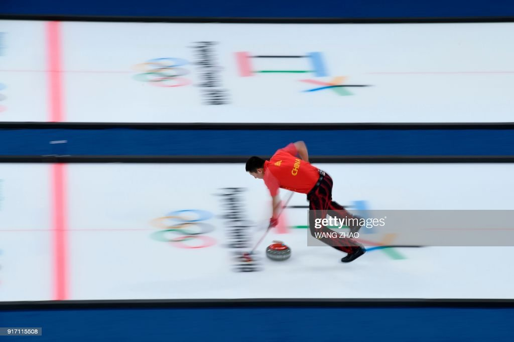 China's Ba Dexin brushes the ice surface during the curling mixed doubles tie-breaker game during the Pyeongchang 2018 Winter Olympic Games at the Gangneung Curling Centre in Gangneung on February 11, 2018. / AFP PHOTO / WANG Zhao