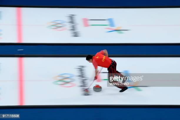 China's Ba Dexin brushes the ice surface during the curling mixed doubles tiebreaker game during the Pyeongchang 2018 Winter Olympic Games at the...