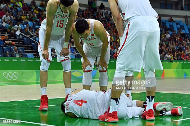 TOPSHOT China's centre Zhou Qi China's forward Li Gen and China's forward Zhai Xiaochuan surround China's guard Zhao Jiwei after he fell during a...