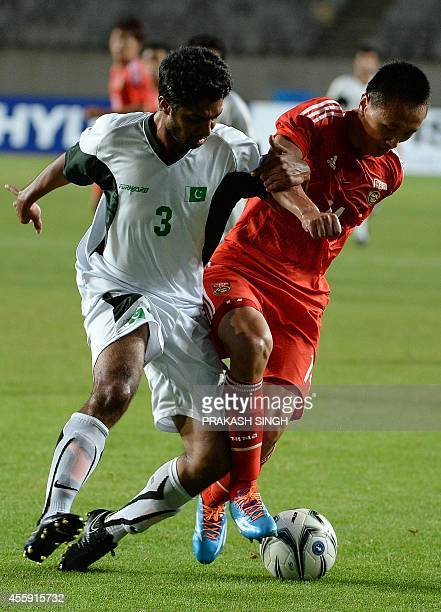 China's Chang Feiya vies for the ball with Pakistan's Muhammad Ahmad during their men's football first round match of the 2014 Asian Games at the...