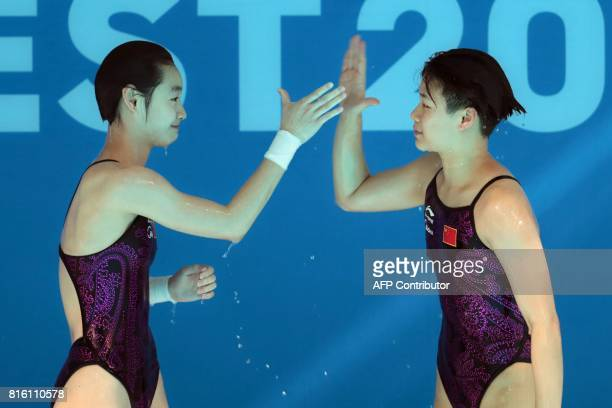 China's Chang Yani and China's Shi Tingmao celebrate their victory in the women's 3m springboard synchro final during the diving competition at the...