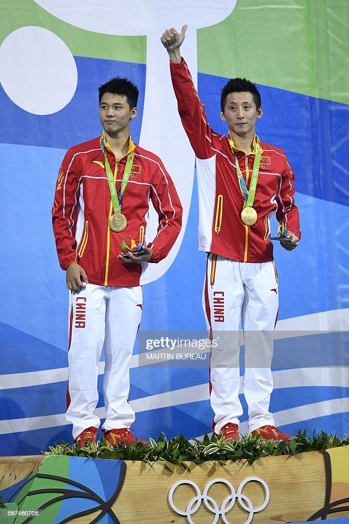 China's Chen Aisen (L) and China's Lin Yue celebrate with their gold medal during the podium ceremony for the Men's Synchronised 10m Platform contest during the diving event at the Rio 2016 Olympic Games at the Maria Lenk Aquatics Centre in Rio de Janeiro on August 8, 2016. / AFP / Martin BUREAU