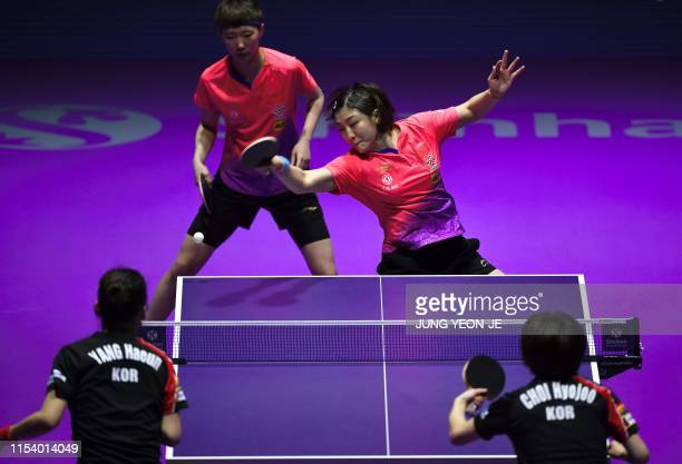 China's Chen Meng returns the ball as teammate Wang Manyu looks on in the women's doubles table tennis final match against South Korea's Choi Hyojoo...
