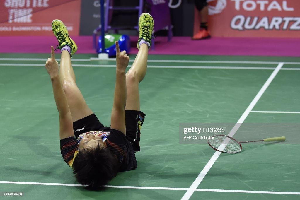 China's Chen Qingchen falls to the floor as she celebrates her win with China's Jia Yifan over Japan's Yuki Fukushima and Sayaka Hirota in their women's doubles final match during the 2017 BWF World Championships of badminton at Emirates Arena in Glasgow on August 27, 2017. /