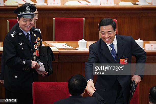 China's Chongqing Municipality Communist Party Secretary Bo Xilai shakes hands with other delegates after the third plenary meeting of the National...