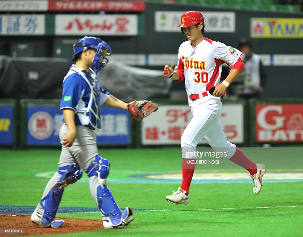 China's Chu Fujia (R) runs to the home-plate as Brazil's catcher Diego Franca (L) looks on following a bases-loaded walk by pitcher Thyago Vieira during the eighth inning of their first-round Pool A game in the World Baseball Classic tournament in Fukuoka on March 5, 2013. China beat Brazil 5-2.